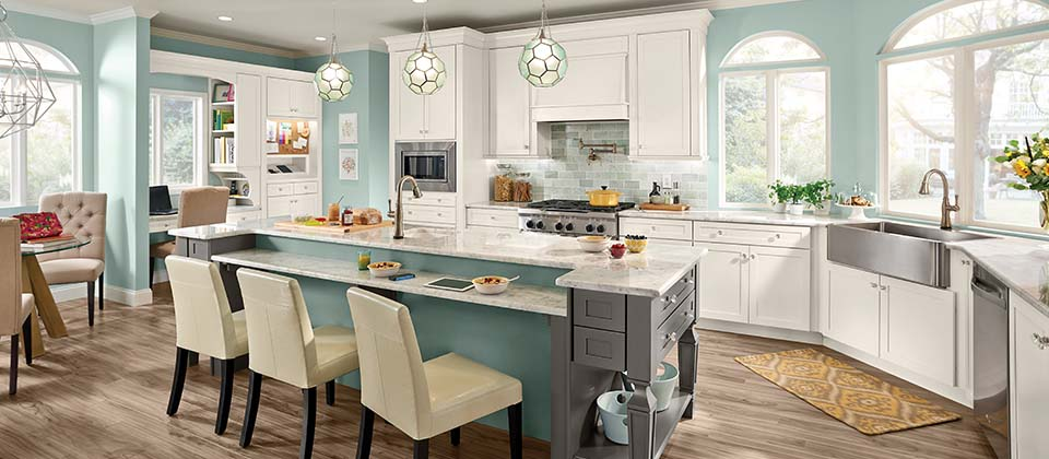 interior design photo of large kitchen with aqua walls and island, white cabinets, stainless appliances and farm sink, grey granite countertops, color matching light fixtures