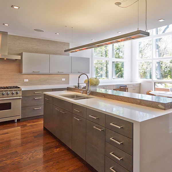 simple modern kitchen with grey Mouser cabinets, white marble surfaces, lots of natural light